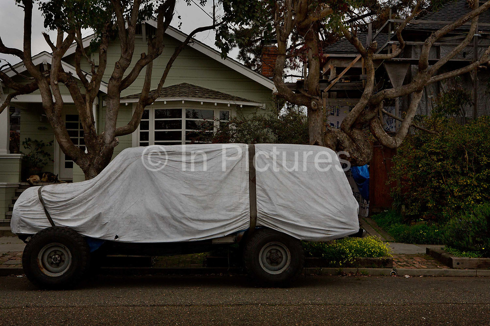 Truck with white cover tied over it parked outside house