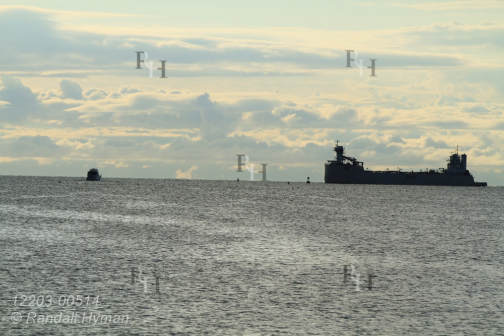 Early morning sky silhouettes boat and freighter on horizon in Thunder Bay; Alpena, Michigan.