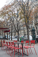 Red metal cafe chairs sit on Boulevard Delessert, lined by tall deciduous tree, in Paris, France. An antique street fountain, parked cars, and building facades are seen in the background.