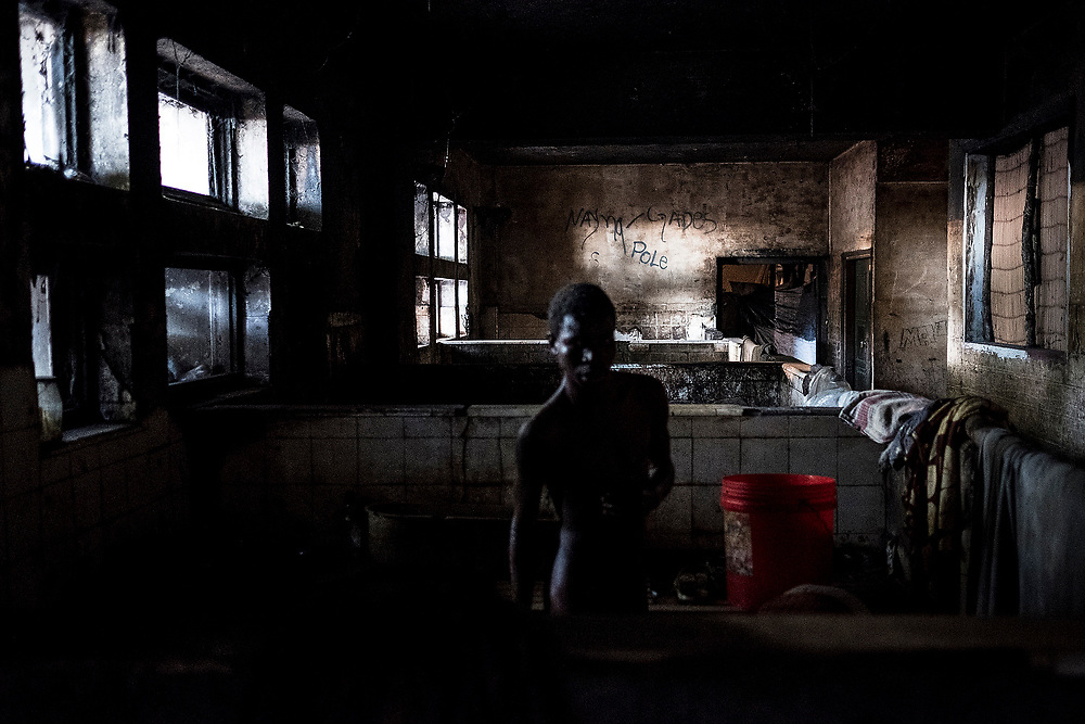 BEIRA, MOZAMBIQUE - JUNE 26, 2016: <br /> Carlos Maganguile, 26 years old, taking a bath in the hotel's old pool bathrooms. He has multiple sclerosis and lives in the old hotel pantries without the slightest conditions with hir mother.
