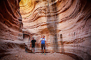 SHOT 10/15/16 1:04:44 PM - Mountain bikers explore a slot canyon along the White Rim Trail. The White Rim is a mountain biking trip in Canyonlands National Park just outside of Moab, Utah. The White Rim Road is a 71.2-mile-long unpaved four-wheel drive road that traverses the top of the White Rim Sandstone formation below the Island in the Sky mesa of Canyonlands National Park in southern Utah in the United States. The road was constructed in the 1950s by the Atomic Energy Commission to provide access for individual prospectors intent on mining uranium deposits for use in nuclear weapons production during the Cold War. Four-wheel drive vehicles and mountain bikes are the most common modes of transport though horseback riding and hiking are also permitted.<br /> (Photo by Marc Piscotty / © 2016)