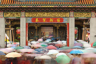 A crowd of people gather in the rain at Lungshan Temple for Chinese Lunar New Year 2007.