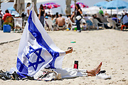 """A woman takes a """"selfie"""" as she is draped with the Israeli national flag during Independence Day celebrations in Tel-Aviv, Israel April 15, 2021. People gathered in their masses at Tel-Aviv's shore line as the Jewish state celebrates 73 years to it's establishment. As vast percentage of the population are vaccinated, celebrations were able to take place in a some what ordinary manner.Starting Sunday April 18, 2021, it will no longer be mandatory to wear a protective mask in open spaces throughout the country."""