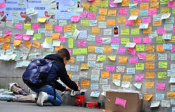 A young girl leaves a message of support on the base of the obelisk on London Bridge, after an unknown 21 year-old man left a box of tape, sticky notes and marker pens with an invite to write a message, following the terror attack in which eight people died.