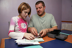 Single parent and young daughter working out bills to pay together and counting money,
