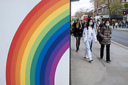 People interacting with a colourful arge scale rainbow on a hoarding outside a shop being refitted on the Kings Road in the upmarket area of Chelsea on 14th April 2021 in London, United Kingdom. Chelsea is one of the principal areas for mid-range, exclusive or luxury goods in West London. It is known as a district where the rich and wealthy shop, mostly for high end ad well as high street fashion and jewellery.