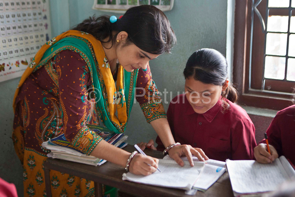 A female Nepalese teacher assess the work of one of her female students in a class room at the GoodWeave centre in Attarkhen, Kathmandu, Nepal.  The children's parents are carpet factory workers, and they have been supported into education by GoodWeave, a charity that works towards getting children out of factories and into education.  Previously these children would have been left unattended in the factory while their parents worked as their low salary could not cover childcare costs. GoodWeave were recipients of the Stars Foundation's Impact Award.