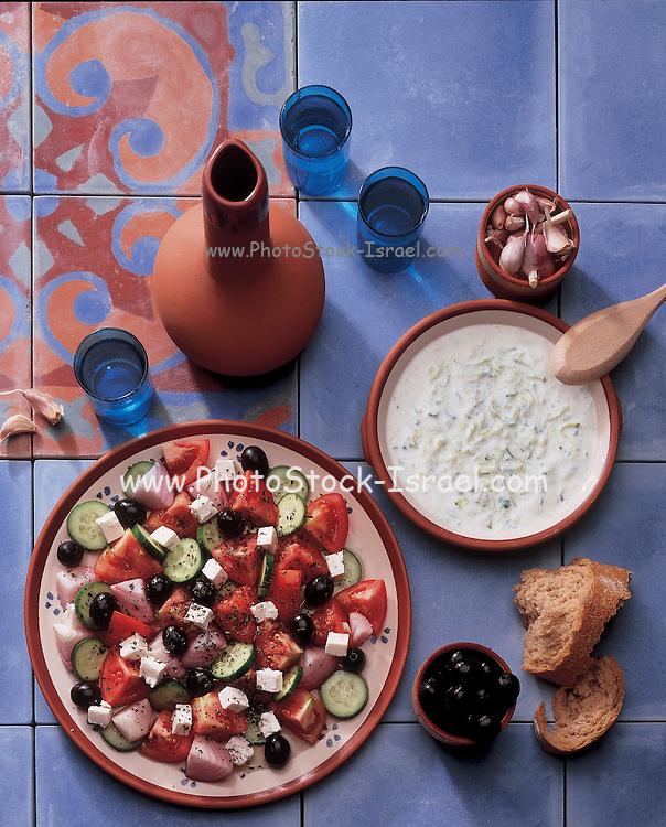 Greek cuisine. Tzatziki, salad, olives, garlic and olive oil