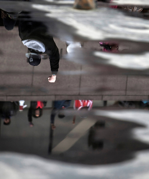 Fists raised in support of Black Lives Matter are reflected in puddles at the Million Artist Movement rally at Government Center in Minneapolis December 13, 2014.