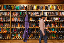 Man walking in front of boots on display in historic M.L Leddy's Boots, Fort Worth Stockyards National Historic District, Fort Worth, Texas, USA.