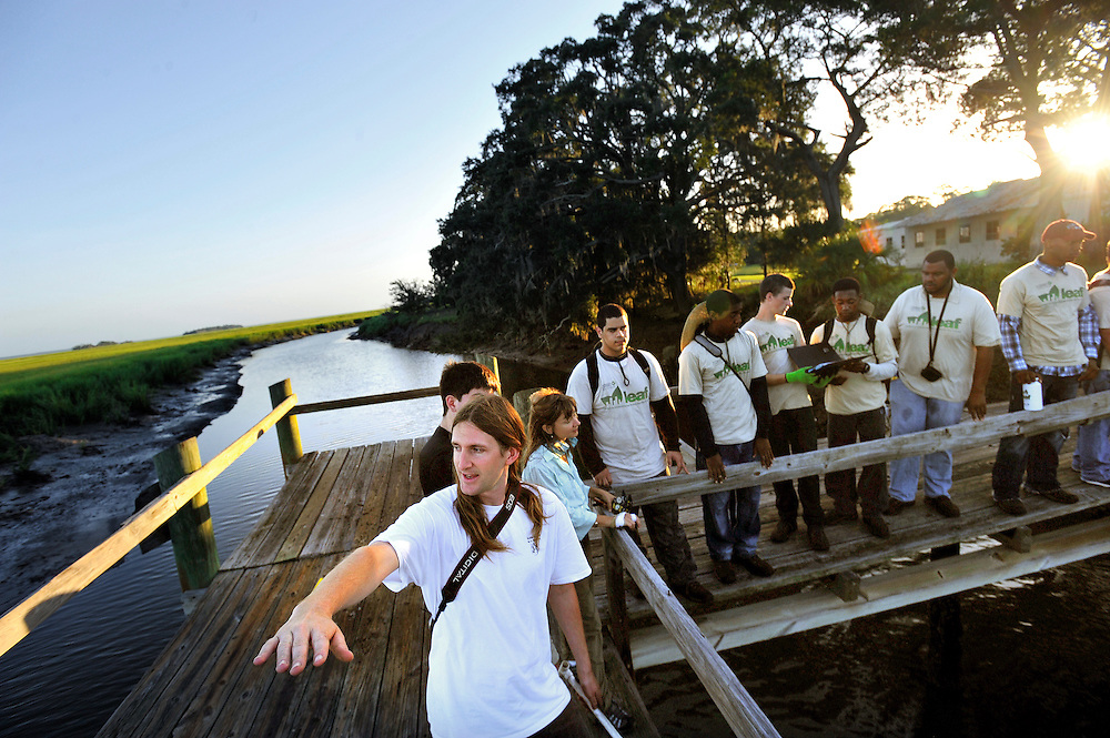 University of Georgia Coordinator for Oyster Restoration, Daniel Harris, foreground, speaks to a group of interns from The Nature Conservancy's Leaders in Environmental Action for the Future (LEAF) program before starting work sampling a oyster reef at the Long Tabby site at low tide on Sapelo Island, Georgia. The LEAF program works with environmental high schools across the nation to combine classroom lessons with real-world conservation work experience for urban youth.(Stephen Morton for The New York Times)..