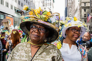 New York, NY - April 16, 2017. Two women with elaborate hats, one with decorations of flowers and butterflies, at New York's annual Easter Bonnet Parade and Festival on Fifth Avenue.