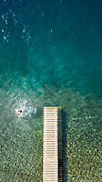 Aerial view of a person jumping from a pontoon in the sea.