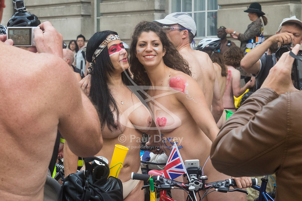 Westminster Bridge, London, June 11th 2016. Hundreds of naked and semi-naked cyclists participate in the World Naked Bike Ride that takes place in cities around the world, to highlight the alternatives to hydrocarbon fuels. PICTURED: Two women pose for a picture.