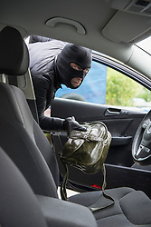 Thief stealing a purse from car seat