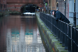 © Licensed to London News Pictures . 29/12/2013 . Manchester , UK . An officer looks over a barrier in to the River Medlock off Oxford Road in Manchester City Centre . The search for 17 year old Adam Pickup from Stockport , who was last seen in the early hours of Saturday 28th December in Manchester City Centre following a night out with friends as , this evening (Sunday 29th December 2013), Greater Manchester Police say they have arrested two men in connection with the teenager's disappearance . Photo credit : Joel Goodman/LNP