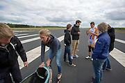 Sebastiaan Bowier (achter in oranje pak) overlegt enkele punten met de technici. Het Human Power Team Delft en Amsterdam (HPT) legt de eerste meters af met de VeloX3, de nieuwe fiets waarmee het HPT in september 2013 hoopt het wereldrecord te breken.<br /> <br /> Rider Sebastiaan Bowier (in orange suite) is discussing some issues on the VeloX3 with the technicians. The Human Power Team Delft and Amsterdam (HPT) is making the first test meters with the VeloX3, the bike with which the team hopes to break the world record in September 2013.