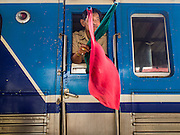 19 MARCH 2015 - AYUTTHAYA, AYUTTHAYA, THAILAND:   A conductor on a train going north from Bangkok to Chiang Mai in the window of his train car in the Ayutthaya station. The train line from Bangkok to Ayutthaya was the first rail built in Thailand and was opened in 1892. The State Railways of Thailand (SRT), established in 1890, operates 4,043 kilometers of meter gauge track that reaches most parts of Thailand. Much of the track and many of the trains are poorly maintained and trains frequently run late. Accidents and mishaps are also commonplace. Successive governments, including the current military government, have promised to upgrade rail services. The military government has signed contracts with China to upgrade rail lines and bring high speed rail to Thailand. Japan has also expressed an interest in working on the Thai train system. Third class train travel is very inexpensive. Many lines are free for Thai citizens and even lines that aren't free are only a few Baht. Many third class tickets are under the equivalent of a dollar. Third class cars are not air-conditioned.   PHOTO BY JACK KURTZ