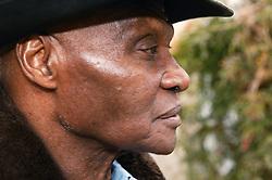 Profile shot of a black elderly man wearing a hat,
