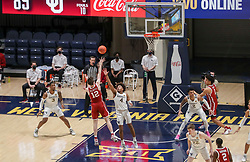 Feb 13, 2021; Morgantown, West Virginia, USA; Oklahoma Sooners guard Austin Reaves (12) shoots in the lane late in the second overtime against the West Virginia Mountaineers at WVU Coliseum. Mandatory Credit: Ben Queen-USA TODAY Sports