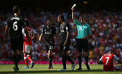 14 August 2016 London - Premier League Football : Arsenal v Liverpool :<br /> Referee Michael Oliver shows a yellow card to Dejan Lovren of Liverpool following a foul on Alexis Sanchez of Arsenal<br /> Photo: Mark Leech