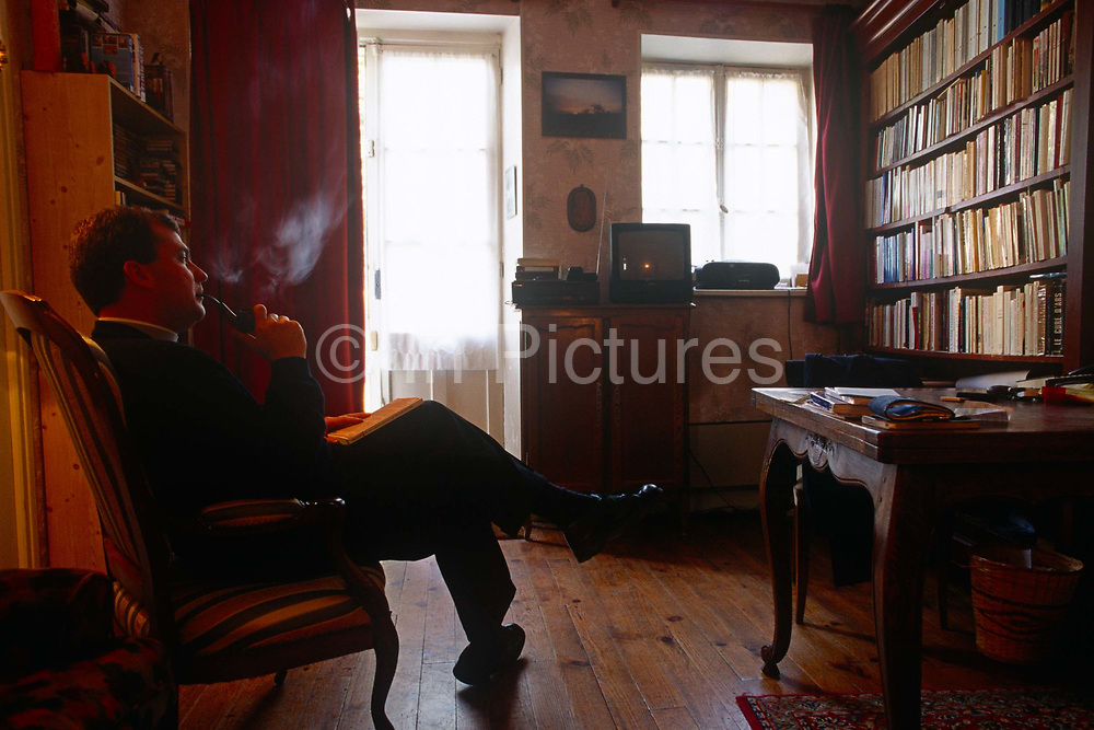 In his private rooms, Father Phillipe Dubos a country priest blows smoke from his pipe in the Presbytry at Equetot a local Catholic church in rural Normandy. With literature lining a bookcase and paperwork on his office table, the priest exhales from his pipe, blowing blue smoke across the study. It is a quiet moment after a busy morning of Mass and community activities. It is estimated that somewhere between 83% to 88% of France's population are Catholic. The church is organised into 98 dioceses, served by 20,523 priests.
