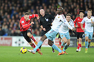 Cardiff City's Craig Bellamy is challenged by West Ham's Alou Diarra during the Barclays Premier league, Cardiff city v West Ham Utd match at the Cardiff city Stadium in Cardiff, South Wales on Saturday 11th Jan 2014.<br /> pic by Jeff Thomas, Andrew Orchard sports photography.