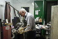 A man shines a brass horse in his brass shining shop in Naples, Italy