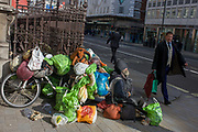 As passers-by walk by, a homeless man sits with all his worldly possessions on Piccadilly in central London. A well-dressed gentleman strides past the vagrant who sits forlornly on the pavement, surrounded by his worldly good - plastic bags attached to an old bike. We see a scene of poverty and privilege - of wealth versus hopelessness - on this prestgious London street where money speaks volumes for those with successful lives.