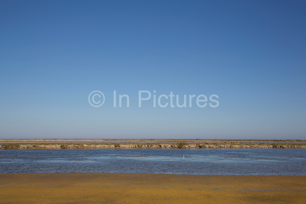 """Famous salt flats at Gruissan, Languedoc-Roussillon, France. This area is very well known for producing sea salt from it's salt fields or marshes on this coastline. Sea salt farms, with giant hills of salt - """"Camelles"""", in differing shades of brown and white, and the flat """"fields"""" of salt water."""