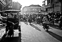 A tuk-tuk driver waits for a fare in front of a busy street market in Phnom Penh, Cambodia