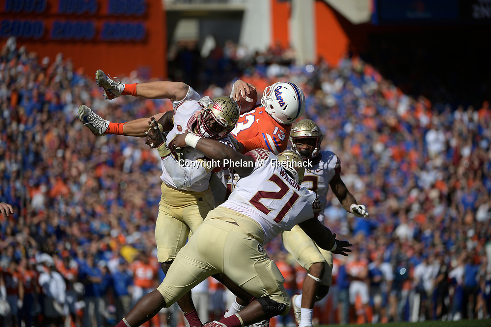 Florida quarterback Feleipe Franks (13) is upended by Florida State linebacker Matthew Thomas (6), defensive back Derwin James (3) and defensive tackle Marvin Wilson (21) on a quarterback keeper during the first half of an NCAA college football game Saturday, Nov. 25, 2017, in Gainesville, Fla. (Photo by Phelan M. Ebenhack)