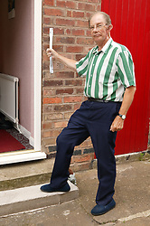 Man with Parkinsons disease using grab rail and half step to help him enter his house,