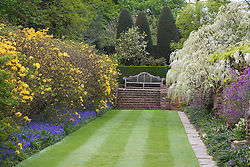 The Moat Walk with azaleas, bluebells and wisteria at Sissinghurst Castle Garden. Wooden bench designed by Edwin Lutyens
