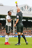 Fulham midfielder Neeskens Kebano (7) is booked by referee Anthony Taylor, yellow card for simulating a dive after a challenge from Oldham Athletic defender Peter Clarke (26) during The FA Cup 3rd round match between Fulham and Oldham Athletic at Craven Cottage, London, England on 6 January 2019.