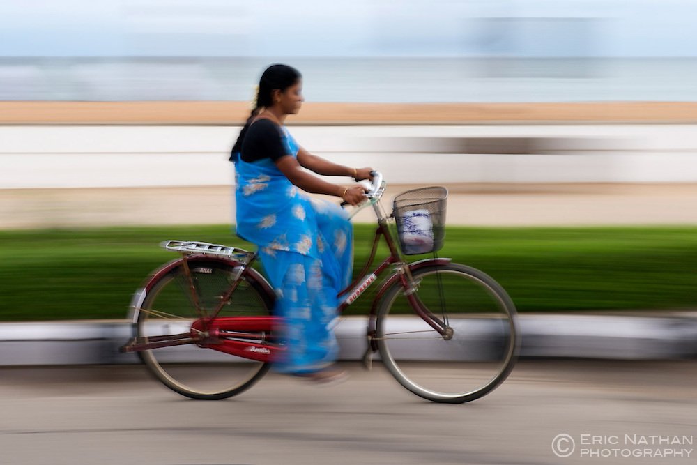 Indian woman cycling on the Pondicherry waterfront in India.