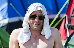 © Licensed to London News Pictures. 25/06/2015. Pilton, UK. Festival atmosphere at Glastonbury Festival 2015 on Thursday Day 2 of the festival.  A man shelters from the sun using a t shirt on a hot sunny morning.This years headline acts include Kanye West, The Who and Florence and the Machine, the latter having been upgraded in the bill to replace original headline act Foo Fighters.   Photo credit: Richard Isaac/LNP