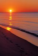 Footprints in the sand on a beach at sunrise - Destin, Florida.