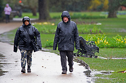 © Licensed to London News Pictures 26/03/2021. Greenwich, UK. Two people look soaking wet from the rain in Greenwich Park, London today during a third national coronavirus lockdown as heavy rain and strong winds make for a wet start to the weekend. Photo credit:Grant Falvey/LNP