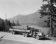 8602-D12. Lake Aldwell was a reservoir that formed behind the Elwha River dam when it was built in 1913. This is how it looked in 1956 when a Port Angeles logging company truck posed beside it for an advertising photo. In 2012, when the dam was removed, the lake drained and the land reverted to forest. Logging truck of Sandberg Logging Co., Port Angeles Washington. 1956