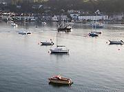 Fishing boat passing yachts at moorings on River Fal, Flushing, Cornwall, England, UK