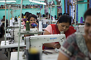 A Nepalese factory worker smiles while cutting a thread with her teeth in Surijha Traders garment factory in Kathmandu, Nepal.  The factory room is full of workers sat at sewing machines. The garments produced in the factory are exported around the world. The factory works closely with the Friends of Needy Children organization in providing fair employment opportunities for young Nepalese men and women.