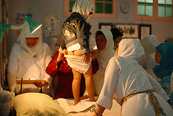 A young girl pulls her panties back up after being circumcised in Bandung, Indonesia on April 23, 2006. The families of 248 girls were given money to have their children circumcised in a mass circumcision celebration timed to honour the Prophet Mohammed's birthday. While religion was the main reason for circumcisions, it is believed by some locals that a girl who is not circumcised would have unclean genitals after she urinates which could lead to cervical cancer. It is also believed if one prays with unclean genitals their prayer won't be heard. The practitioners used scissors to cut the hood and tip of the clitoris. The World Health Organization has deemed the ritual unnecessary and condemns such practices.