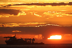 The sun rises behind the Nor Atlantis offshore supply ship of the coast of Blyth.