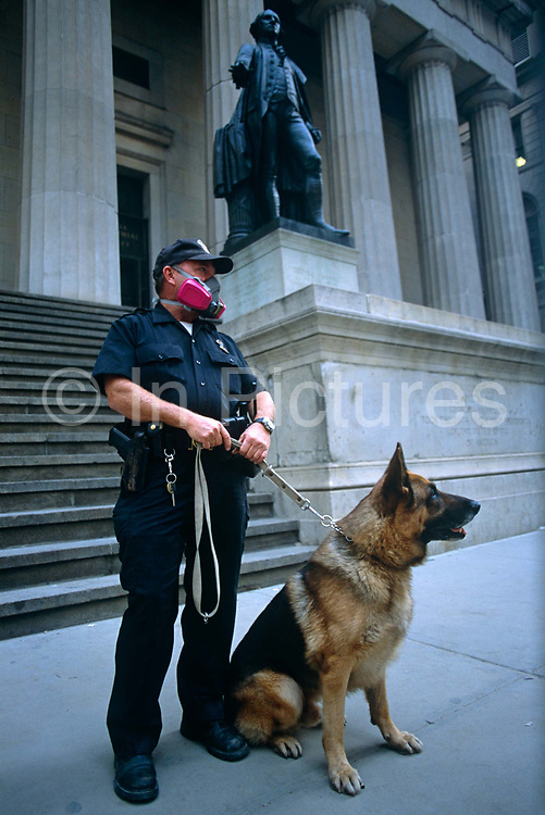 The Monday morning following the attacks on September 11th we see a member of the National Guard wearing a dust mask while standing with his German Shepherd Alsatian dog beneath the high columns of the Federal Hall, located in Wall Street. It was the first capitol of the United States of America and the site of George Washington's first inauguration in 1789 whose statue stands above. It is also the place where the United States Bill of Rights was passed. To celebrate the near-return to financial normality, New Yorkers' spirit was proved intact by the hanging of US flags from buildings. Days after the historical events, security was prominent at all nationally symbolic institutions and buildings. As a show of force, it was also a clear deterrent for would-be criminals when New Yorkers felt vulnerable to further attack.