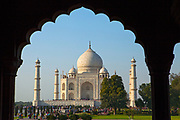 The Taj Mahal at sunrise through an arch. It is an ivory-white marble mausoleum on the southern bank of the river Yamuna in the Indian city of Agra