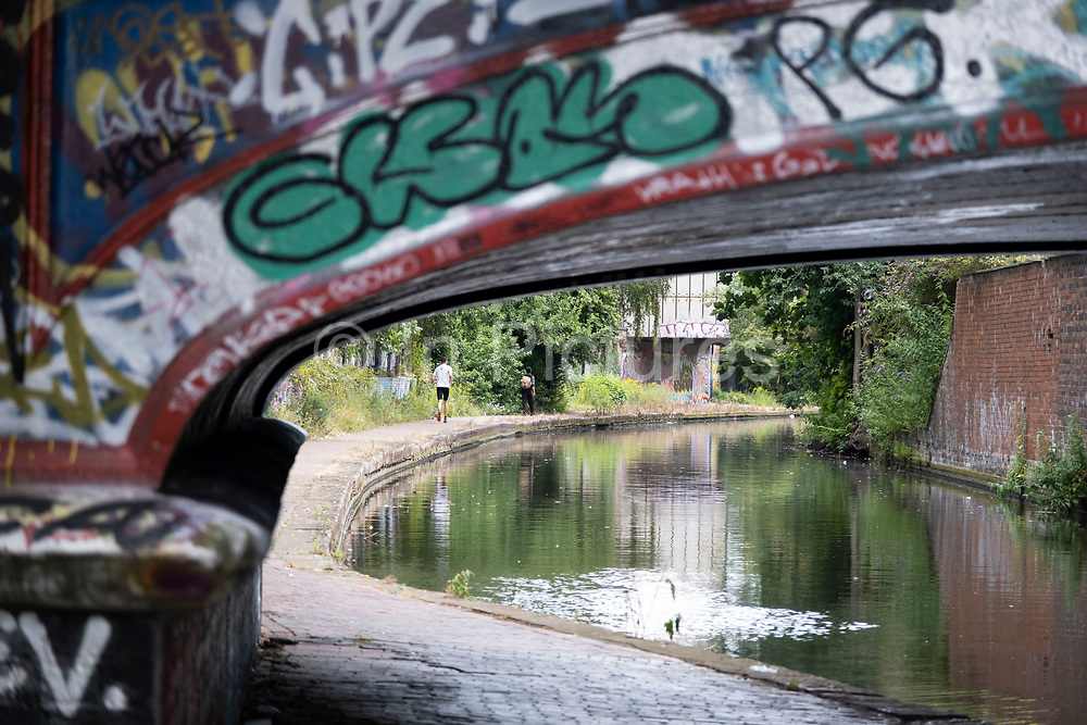 Scene with graffiti along the Grand Union Canal, very close to the city centre on 3rd August 2020 in Birmingham, United Kingdom. Birmingham has around 35 miles of canals, said to be more than in Venice, and are very much a reminder of a Birminghams industrial heritage. During the Industrial Revolution these canals were busy, transporting heavy goods like coal, iron, while playing a pivotal role in the development of Birmingham as an industrial powerhouse.
