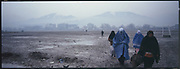 Women walk across a large filed that is sometimes used as a soccer field in Kabul.