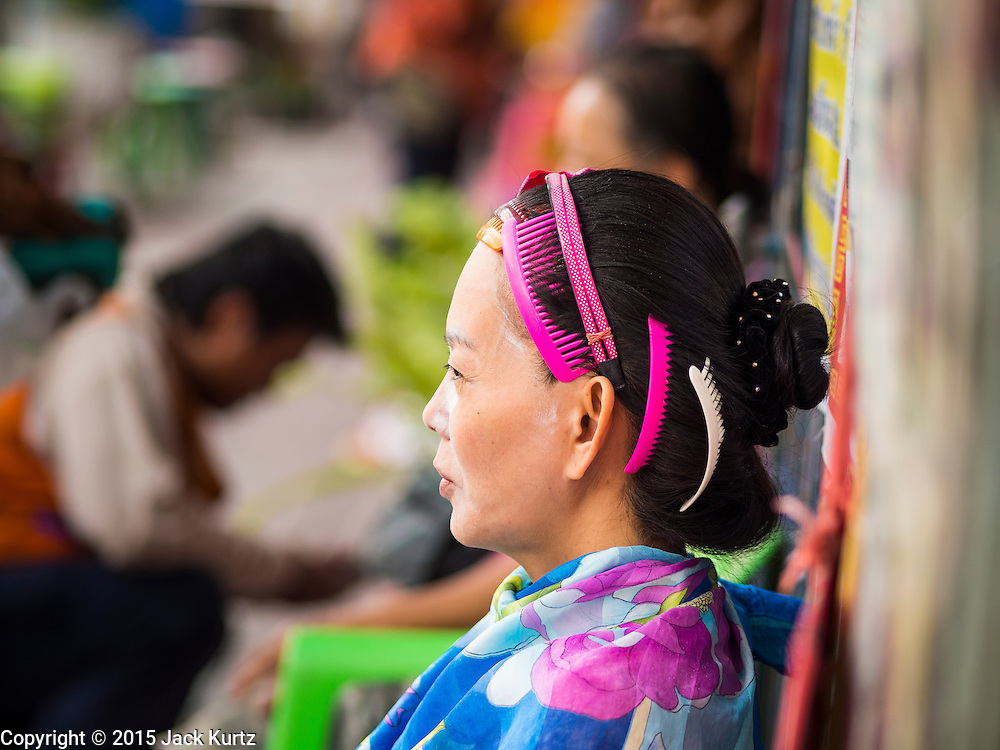 """17 FEBRUARY 2015 - BANGKOK, THAILAND:  A woman waits to be worked on at a threading stand on Charoen Krung Road in Bangkok's Chinatown. About a dozen people, mostly women, have set up shop on the sidewalk to do hair removal for clients. They use thread to remove hair, a practice called """"threading"""" which originated in India more than 6,000 years ago. It's growing in popularity in the US and Europe as an alternative to waxing. A cotton or polyester thread is pulled along unwanted hair in a twisting motion, the hair is trapped in a mini lasso, and lifted out of the follicle.   PHOTO BY JACK KURTZ"""