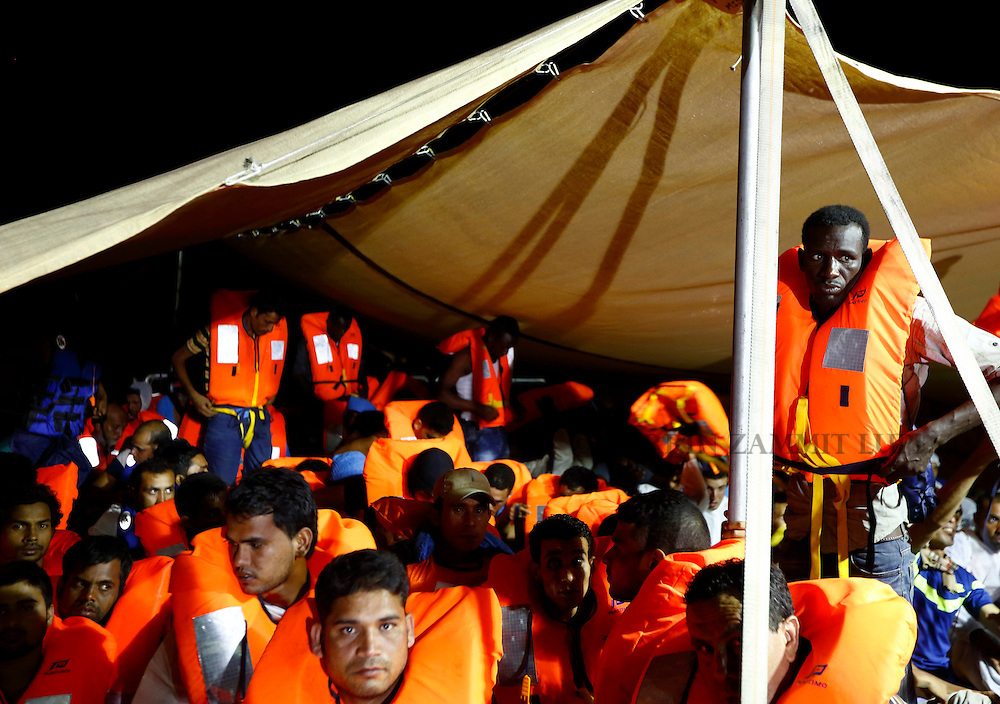 Migrants on the Migrant Offshore Aid Station (MOAS) ship MV Phoenix wait to be transferred to the Norwegian ship Siem Pilot off the coast of Libya August 6, 2015.  An estimated 700 migrants on an overloaded wooden boat were rescued 10.5 miles (16 kilometres) off the coast of Libya by the international non-governmental organisations Medecins san Frontiere (MSF) and MOAS without loss of life on Thursday afternoon, according to MSF and MOAS, a day after more than 200 migrants are feared to have drowned in the latest Mediterranean boat tragedy after rescuers saved over 370 people from a capsized boat thought to be carrying 600.<br /> REUTERS/Darrin Zammit Lupi <br /> MALTA OUT. NO COMMERCIAL OR EDITORIAL SALES IN MALTA